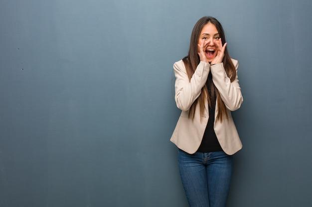 Jonge bedrijfsvrouw die iets gelukkig aan de voorzijde schreeuwt
