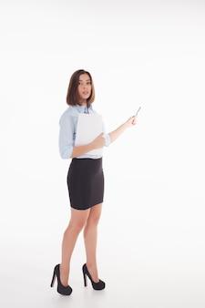 Jonge bedrijfsvrouw die iets op de witte achtergrond toont