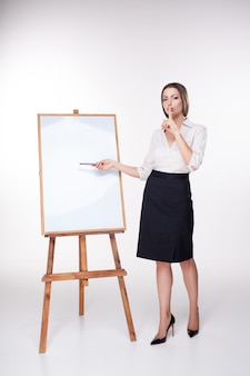 Jonge bedrijfsvrouw die iets op de witte muur toont