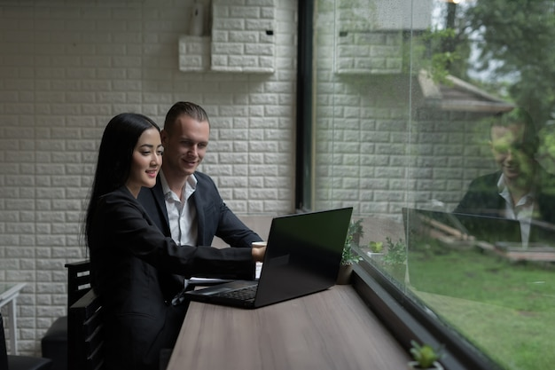 Jonge bedrijfsvrouw die iets toont om zakenman die op haar laptop wordt gezien te rijpen