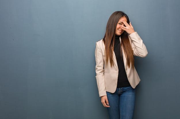 Jonge bedrijfsvrouw die in verlegenheid wordt gebracht en tegelijkertijd lacht