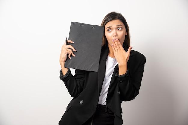 Jonge bedrijfsvrouw die klembord toont.