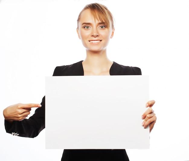 Jonge bedrijfsvrouw die leeg aanplakbiljet toont