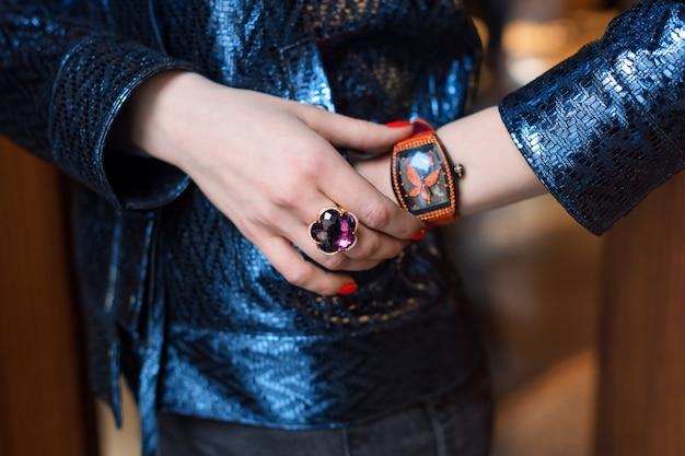 Jonge bedrijfsvrouw die luxehorloge en kostbare juwelen draagt. stijlvolle damesaccessoires.
