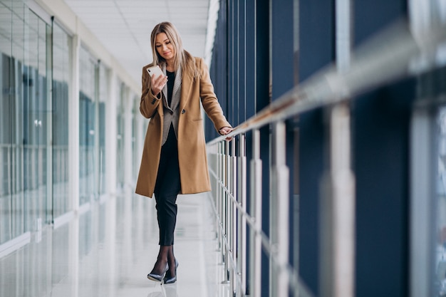 Jonge bedrijfsvrouw die op de telefoon in een luchthaven spreekt