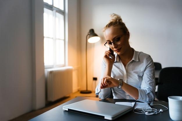 Jonge bedrijfsvrouw die op de telefoon in haar bureau spreekt