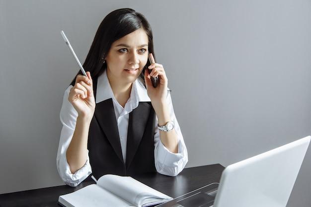 Jonge bedrijfsvrouw die op de telefoon spreekt en nota's in een notitieboekje in het bureau maakt