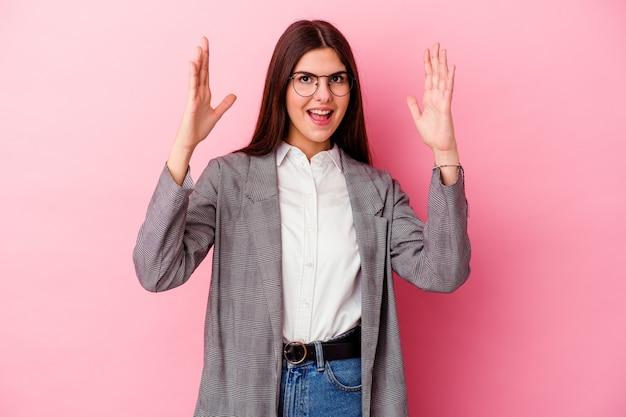 Jonge bedrijfsvrouw die op roze muur wordt geïsoleerd die een aangename opgewonden verrassing ontvangt en handen opheft