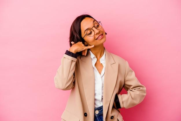 Jonge bedrijfsvrouw die op roze muur wordt geïsoleerd die een mobiel telefoongesprekgebaar met vingers toont