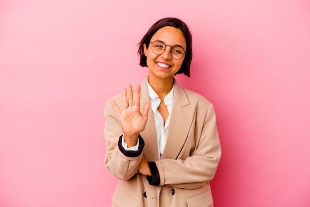 Jonge bedrijfsvrouw die op roze muur wordt geïsoleerd die vrolijk glimlachend nummer vijf toont met vingers