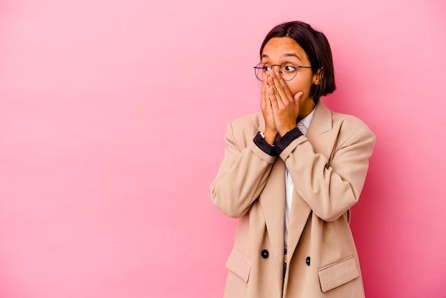 Jonge bedrijfsvrouw die op roze muur wordt geïsoleerd het nadenkende op zoek naar een exemplaarruimte die mond behandelt met hand