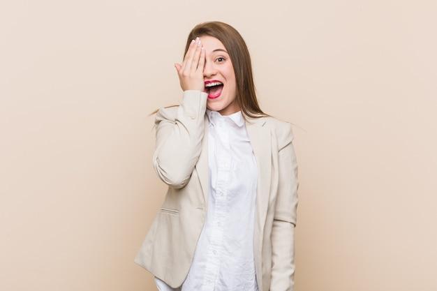 Jonge bedrijfsvrouw die pret heeft die de helft van gezicht behandelt met palm.