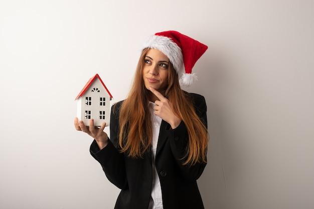 Jonge bedrijfsvrouw die santahoed het vieren kerstmisdag draagt