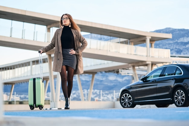 Jonge bedrijfsvrouw die tegen zwarte luxeauto loopt