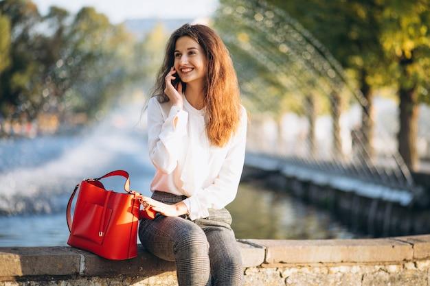 Jonge bedrijfsvrouw die telefoon in park met behulp van tijdens lunchtijd