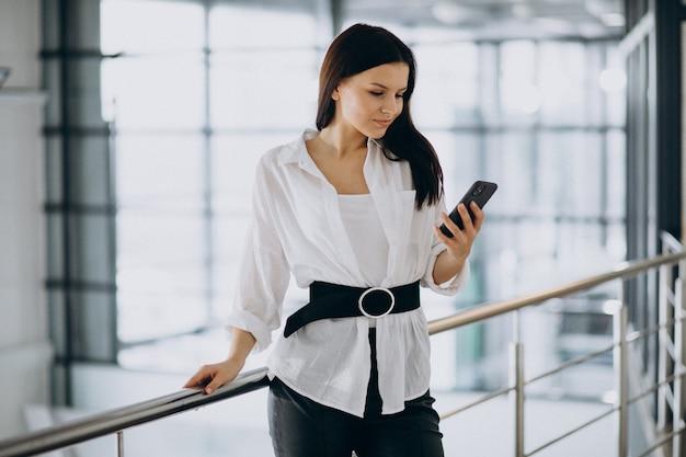 Jonge bedrijfsvrouw die telefoon met behulp van op het kantoor