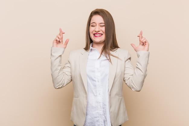 Jonge bedrijfsvrouw die vingers kruist voor het hebben van geluk