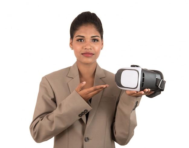 Jonge bedrijfsvrouw die & vr-het apparaat van hoofdtelefoonglazen houdt toont dat op witte ruimte wordt geïsoleerd
