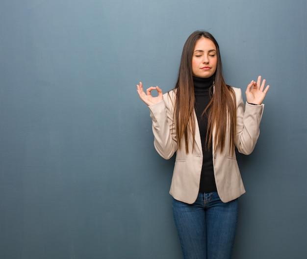 Jonge bedrijfsvrouw die yoga uitvoert