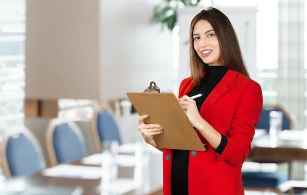 Jonge bedrijfsvrouw die zich met haar klembord bevindt