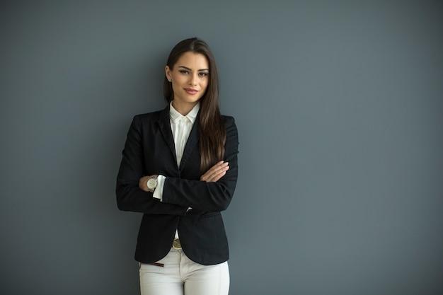 Jonge bedrijfsvrouw door de muur