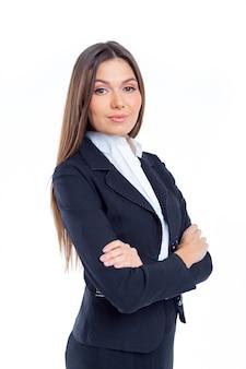Jonge bedrijfsvrouw in bureauuitrusting die zich met gekruiste die wapens bevinden, op wit worden geïsoleerd