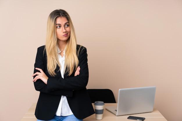 Jonge bedrijfsvrouw in een bureau dat een idee denkt