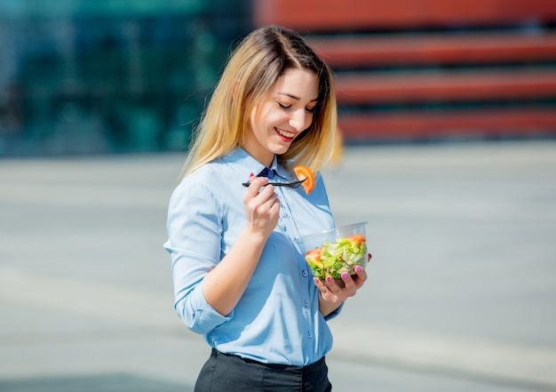 Jonge bedrijfsvrouw met de doos van de saladalunch op openlucht