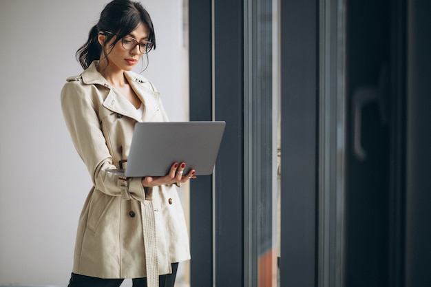 Jonge bedrijfsvrouw met laptop die zich door het venster in bureau bevindt