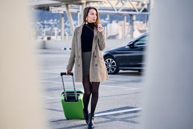 Jonge bedrijfsvrouw tegen zwarte luxeauto