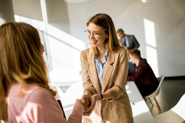 Jonge bedrijfsvrouwen die vriendschappelijke handdruk in het bureau geven