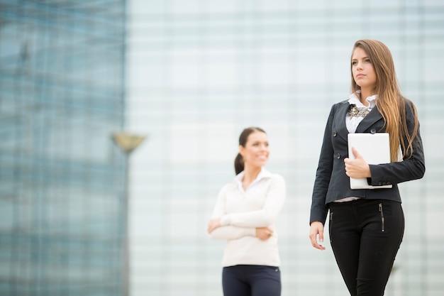 Jonge bedrijfsvrouwen voor de bureaubouw