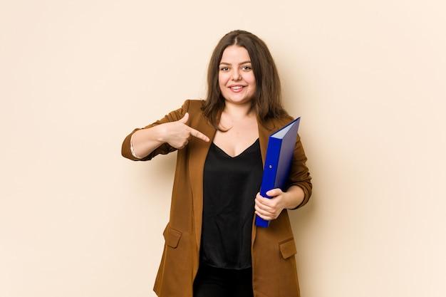 Jonge bedrijfsvrouwenbedrijfsdossier die met de hand naar een ruimte van het overhemdsexemplaar richten, trots en zeker