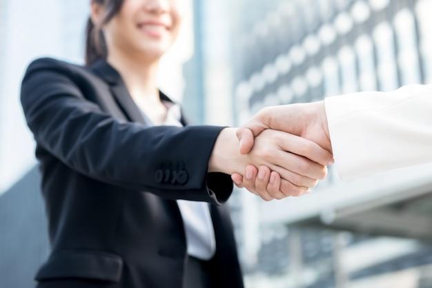 Jonge bedrijfsvrouwenleider die handdruk met haar partner maakt