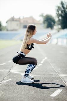 Jonge, behoorlijk goed gebouwde sportvrouw die doelgericht naar voren kijkt en ijverig squats doet met elastische band op een buitenstadion