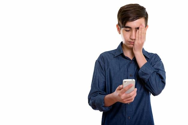 Jonge beklemtoonde perzische tiener die mobiele telefoon met behulp van