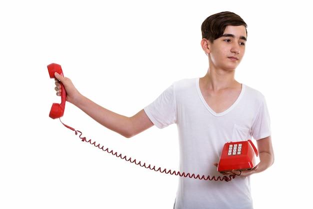 Jonge beklemtoonde perzische tiener die oude telefoon houdt