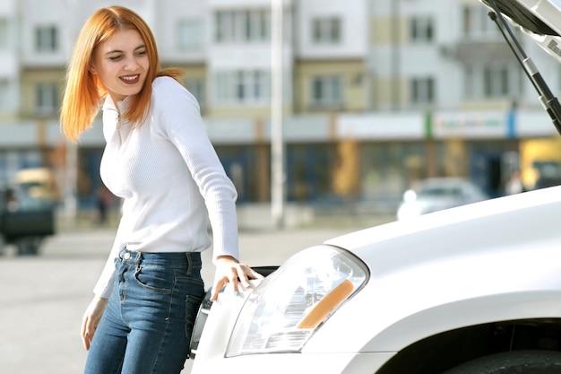 Jonge beklemtoonde vrouwenbestuurder dichtbij gebroken auto met geknalde kap die een prbreakdownprobleem heeft met haar voertuig dat op hulp wacht.