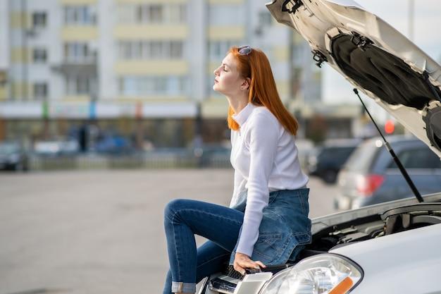 Jonge beklemtoonde vrouwenbestuurder dichtbij gebroken auto met geknalde kap die op hulp wacht.