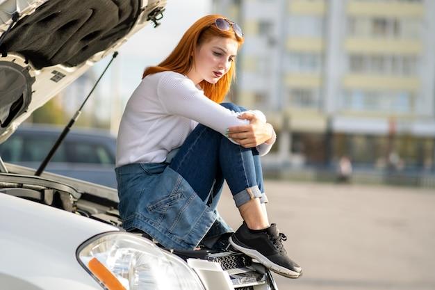 Jonge beklemtoonde vrouwenbestuurder dichtbij gebroken auto met geknalde kap die op hulp wacht