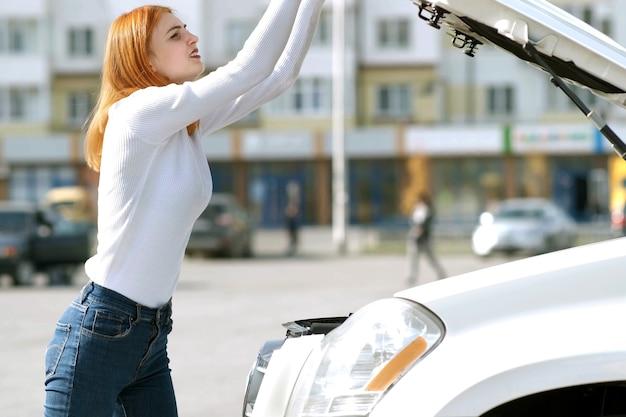 Jonge beklemtoonde vrouwenbestuurder dichtbij kapotte auto met geklapte motorkap die een prbreakdownprobleem heeft met haar voertuig dat op hulp wacht.