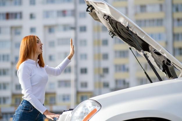 Jonge beklemtoonde vrouwenbestuurder die zich dichtbij broked auto met open kap bevinden.