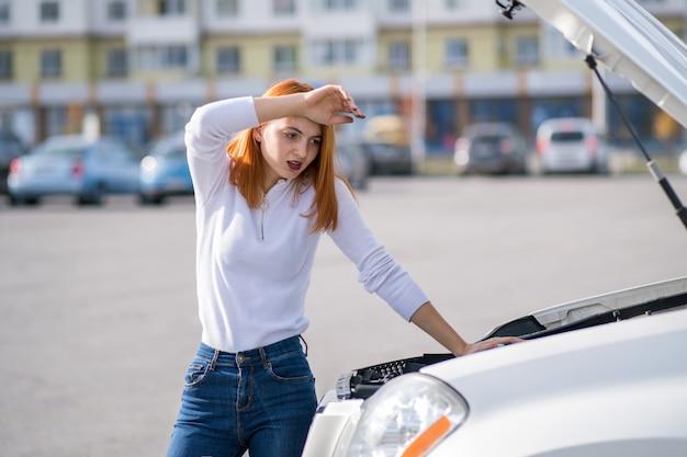 Jonge beklemtoonde vrouwenbestuurder die zich dichtbij broked auto met open kap bevindt