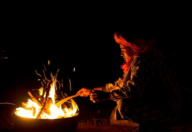 Jonge berber man zit bij kampvuur