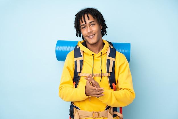 Jonge bergbeklimmer afro-amerikaanse man met een grote rugzak geïsoleerd op een blauwe applaudisseren