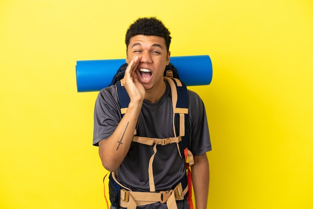 Jonge bergbeklimmer afro-amerikaanse man met een grote rugzak geïsoleerd op een gele achtergrond die met wijd open mond schreeuwt