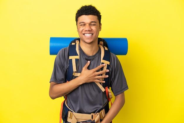 Jonge bergbeklimmer afro-amerikaanse man met een grote rugzak geïsoleerd op een gele achtergrond die veel lacht