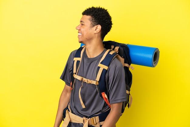 Jonge bergbeklimmer afro-amerikaanse man met een grote rugzak geïsoleerd op gele achtergrond lachen in zijpositie
