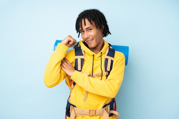 Jonge bergbeklimmer afro-amerikaanse man met een grote rugzak op een blauwe muur sterke gebaar maken