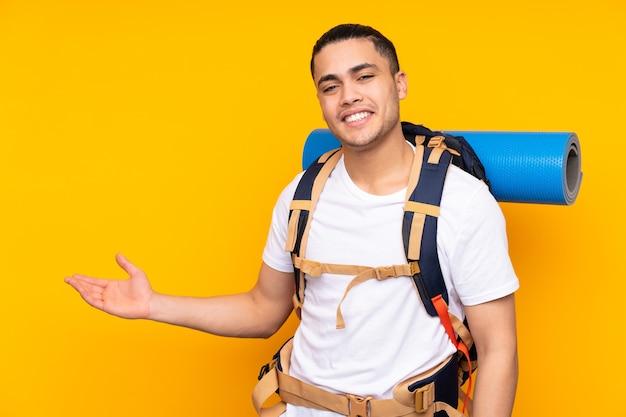Jonge bergbeklimmer aziatische man met een grote rugzak geïsoleerd op geel bedrijf copyspace denkbeeldig op de palm